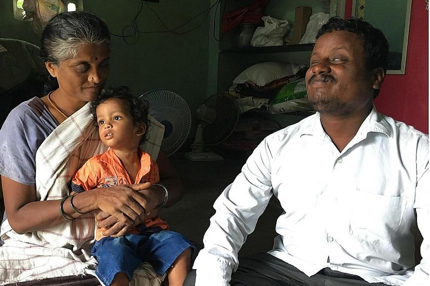 Mr Dharman and his wife Uganthai with their two-year-old son Rohit. The couple used to sell items on local trains to earn a living, but lost their income after rail services were halted.