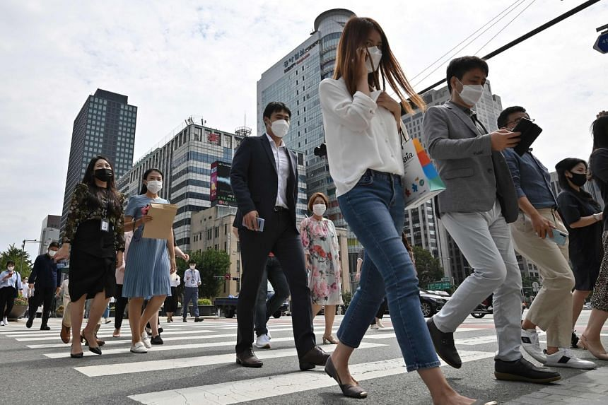 People wearing face masks cross a road in Seoul, on Sept 11, 2020.South Korea's early success in containing the pandemic was thwarted by a mid-August rally that led to another massive outbreak in the country.