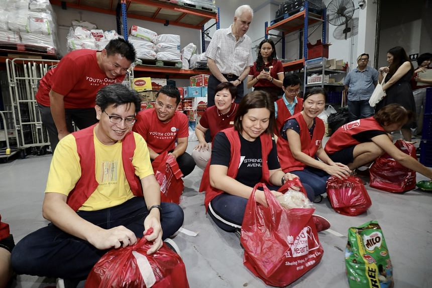 Mr Desmond Lee (in red, squatting), who is now National Development Minister and co-chairman of the Emerging Stronger Task Force, launching the SGUnited Portal, which brings together community-led Covid-19 responses, in February. LIANHE ZAOBAO FILE P