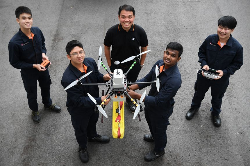 ITE aerospace avionics lecturer Soh Kee Teck (centre) and students (from left) Stephen Ong, Erhan Harith Abdul Malik, Sanjay Shagaran and Kenneth Ng with a drone they are developing to patrol beaches. It carries a float that can be dropped near a swi