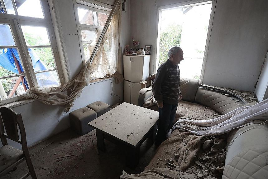 An Armenian surveying the damage to his house in Nagorno-Karabakh yesterday, after recent shelling by Azeri forces. A video grab allegedly showing an Azeri artillery strike towards the positions of Armenian separatists in Nagorno-Karabakh. The fierce