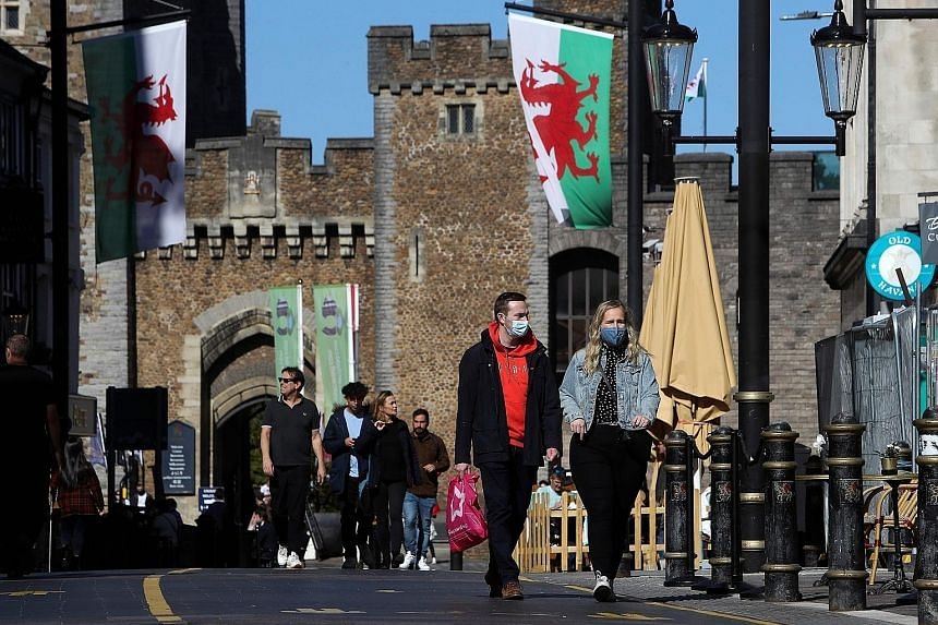 People walking in the city of Cardiff, in the south of Wales, on Sunday. A British newspaper reported that ministers were preparing to enforce a total social lockdown across much of northern England and potentially London.