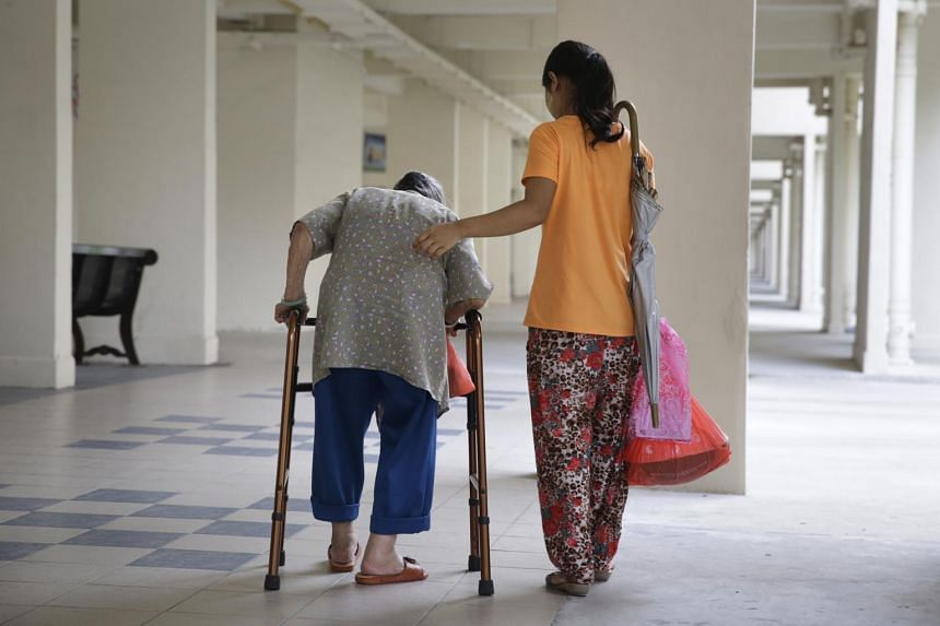 A domestic helper assisting an elderly lady to walk with an aid.