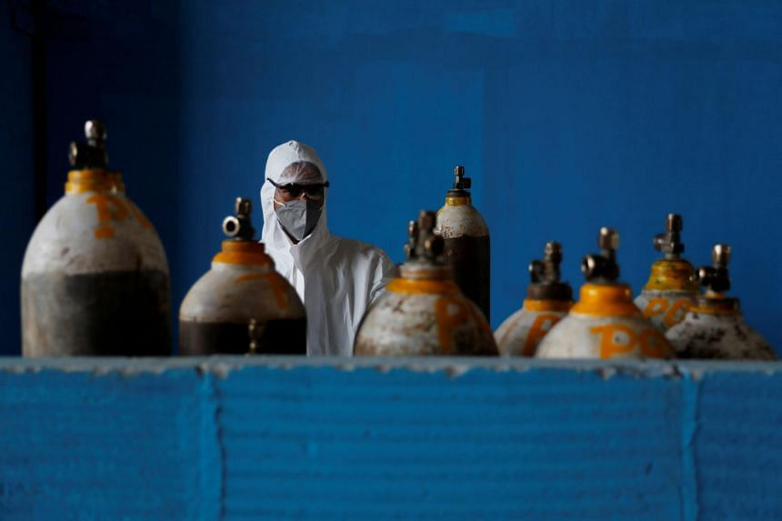 A medical worker stands next to an oxygen cylinder at the Yatharth Hospital in Noida, India, on Sept 15, 2020.