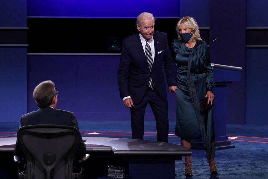 Democratic presidential nominee Joe Biden and his wife Jill Biden speak to debate moderator Chris Wallace.
