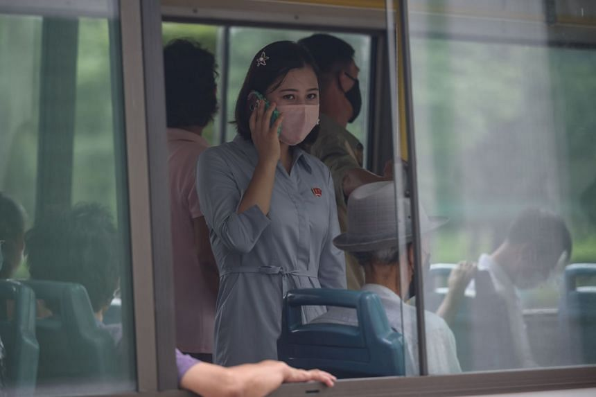 A woman speaks on a mobile phone as she rides a bus in Pyongyang on Aug 13, 2020.