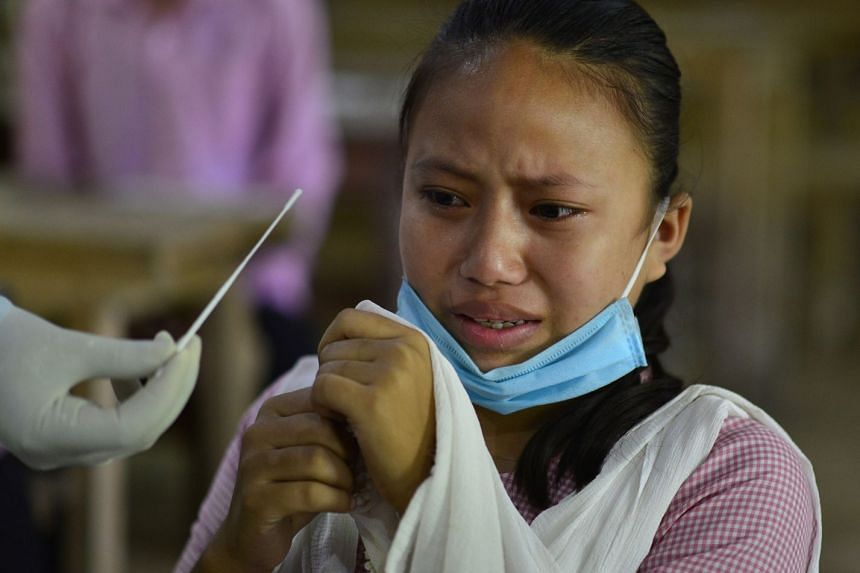 A student reacts as a health worker prepares to collect a swab sample at a school in Assam, India.