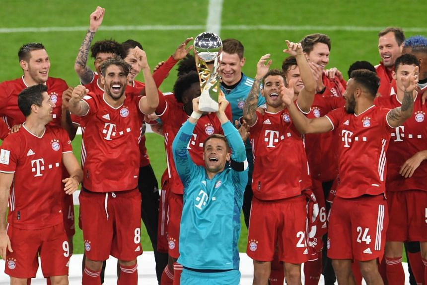 Bayern goalkeeper Manuel Neuer and teammates celebrate with the trophy after winning the German Super Cup.