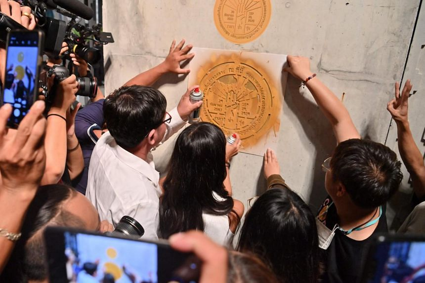 Protesters paint a marker representing the brass plaque that was removed by Thai authorities, during a rally in Bangkok on Sept 24, 2020.