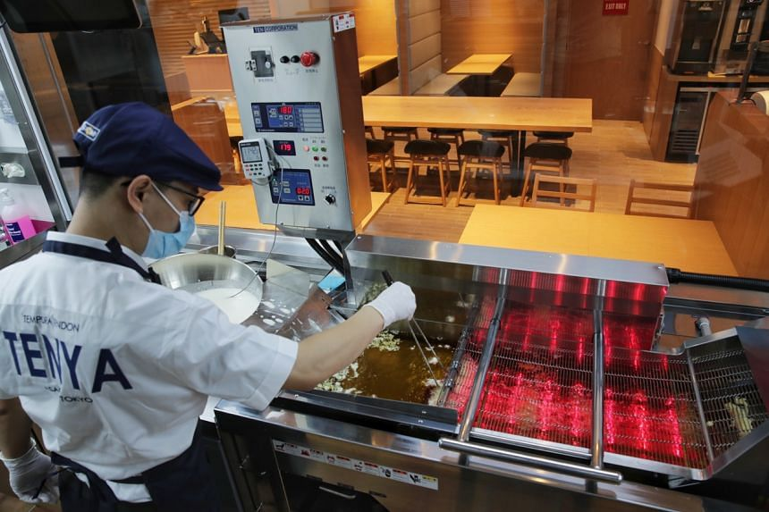 A kitchen staff demonstrates the use of the Automatic Fryer at Tenya Tendon at Orchard Central on Sept 24, 2020.
