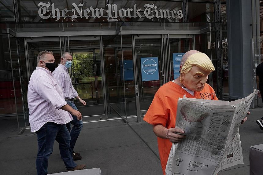 Activist Mike Hisey dressed as President Donald Trump in a prison jumpsuit reading The New York Times in front of the paper's office in Manhattan, New York City, last month.