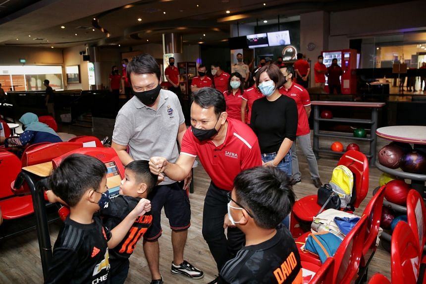 Senior Minister of State for Defence and Safra president Zaqy Mohamad (in red) during a tour of the Safra Yishun clubhouse.