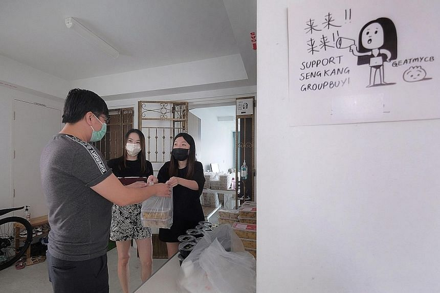 Ms Ashley Teo (in white mask) and Ms Cheryl Guo (in black mask) distributing food orders to a nearby resident from Ms Teo's home in Sengkang. They co-host Sengkang Group Buy, compiling orders in the neighbourhood for hawker food, fruit, cakes, and ev