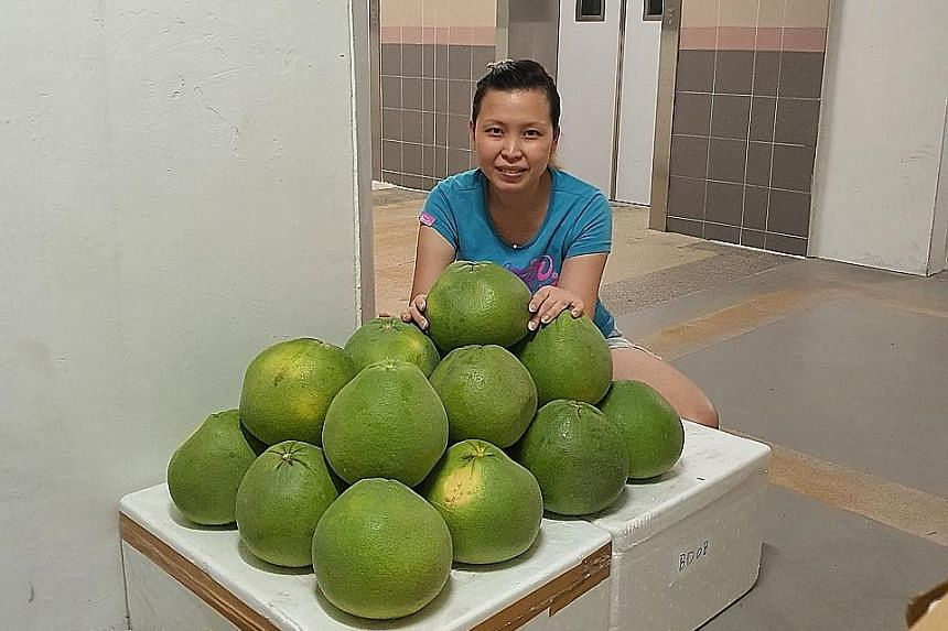 Mrs Kelly Sia, a host for GroupBuysSG, with a bulk order of pomelos. Some other items ordered by the group include snowskin mooncakes from Raffles Singapore and milk from Hokkaido.