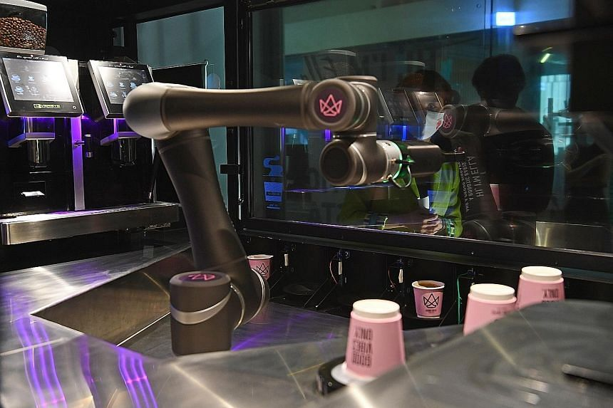 Singapore's first fully automated robot barista, Ella, brews and serves coffee behind a transparent screen in a contactless set-up. Users have to download the Crown Coffee mobile app to order drinks. ST PHOTO: DESMOND FOO