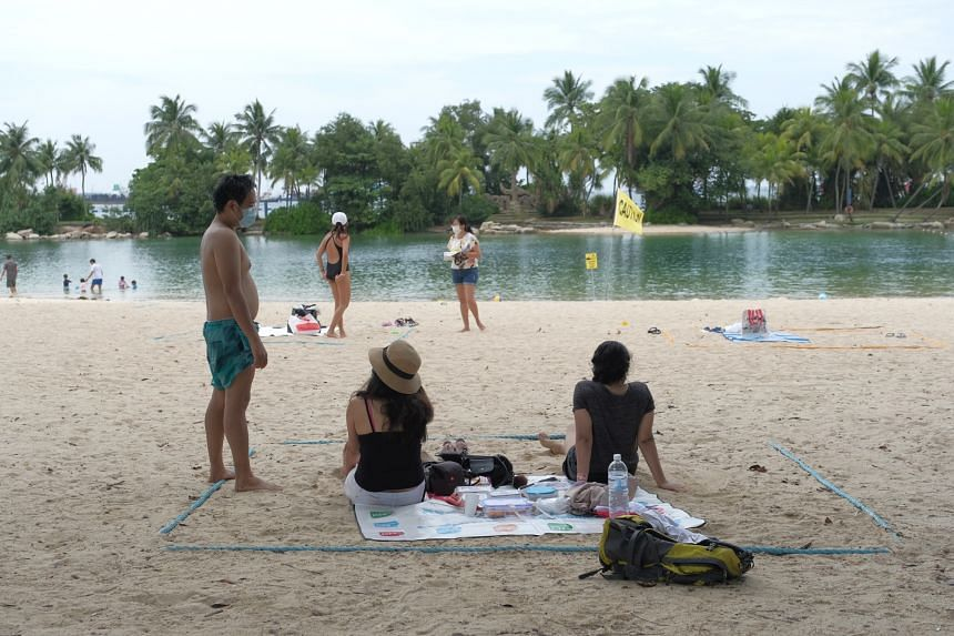 """People at Palawan beach sitting inside a """"safety ring"""", which indicates where a group of five may gather, on Oct 4, 2020."""