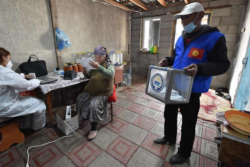 A woman looks through her ballot paper on the eve of the main day of Kyrgyzstan's parliamentary election, on Oct 3, 2020.