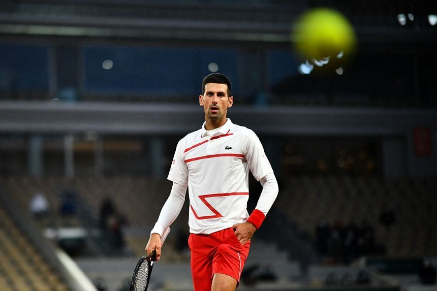 Djokovic receives balls from a ball boy as he plays against Colombia's Daniel Galan.
