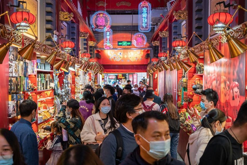 Shoppers are seen in a street lined with souvenir shops in Beijing, on Oct 4, 2020.