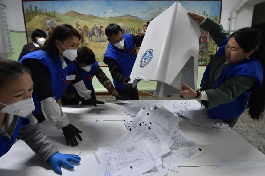 Members of a local electoral commission empty a ballot box to count votes on Oct 4, 2020.