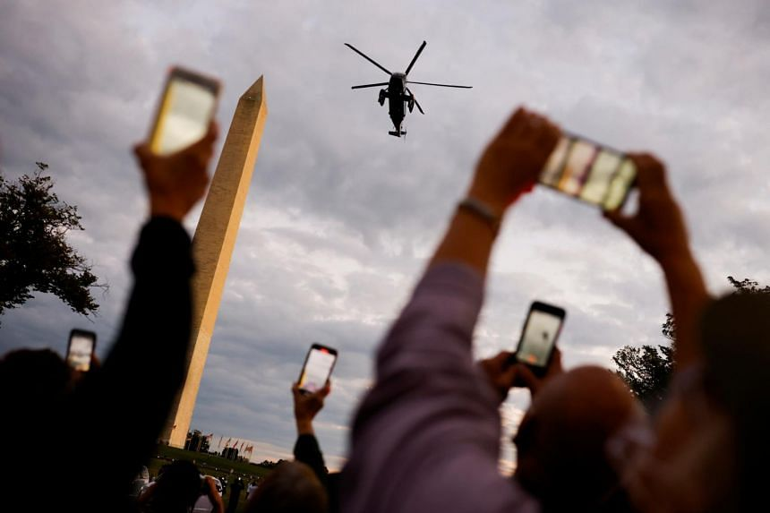 People take pictures of Marine One as it flies President Donald Trump to the White House in Washington on Oct 5, 2020.