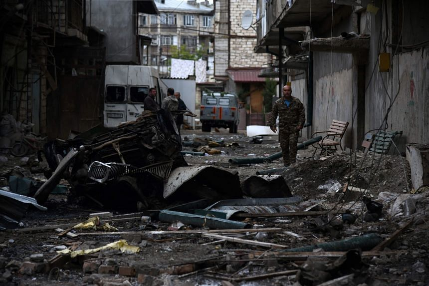 Above: The aftermath of recent shelling during the ongoing fighting between Armenia and Azerbaijan over the breakaway Nagorno-Karabakh region, in the disputed region's main city of Stepanakert on Sunday. Left: People seeking shelter in the basement o