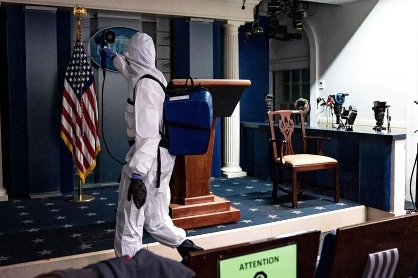A member of the White House cleaning staff sprays disinfectant in the press briefing room in Washington on Oct 5, 2020.