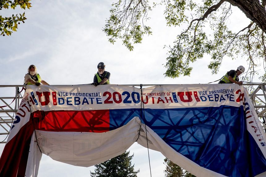 Workers hanging a banner outside Kingsbury Hall at the University of Utah in Salt Lake City, ahead of today's vice-presidential debate between Republican Mike Pence and his challenger, Democrat Kamala Harris.