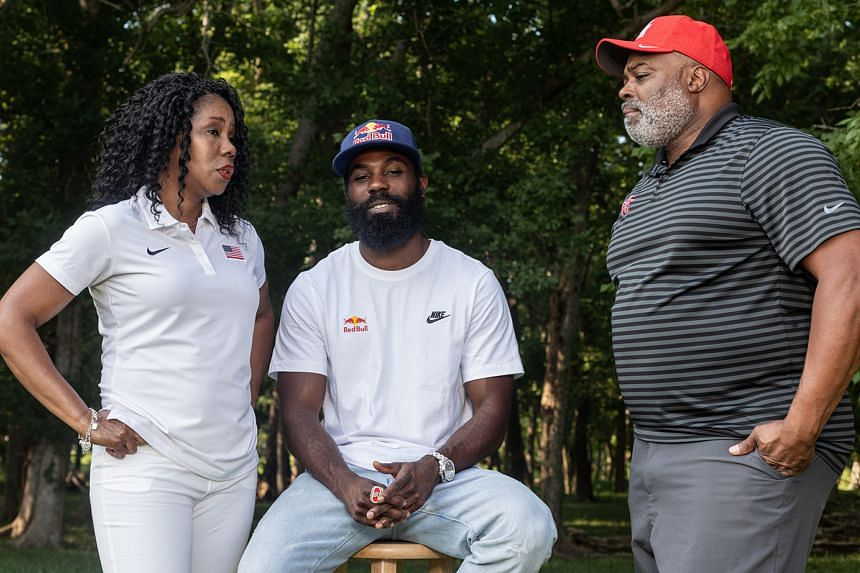 Cameron Burrell, flanked by parents Michelle and Leroy, both Olympic sprint relay gold medallists, at their home in Missouri City, Texas.