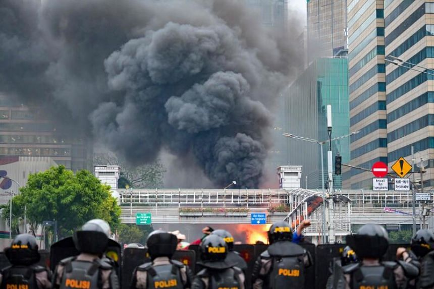 Smoke rising from a fire at a bus station during clashes in Jakarta on Oct 8, 2020.