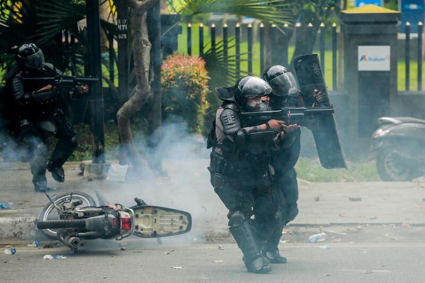 Policemen firing tear gas at protesters during a demonstration in Medan, North Sumatra, on Oct 8, 2020.