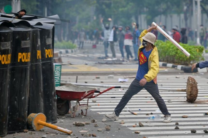 An activist attacking police officers during clashes in Jakarta on Oct 8, 2020.