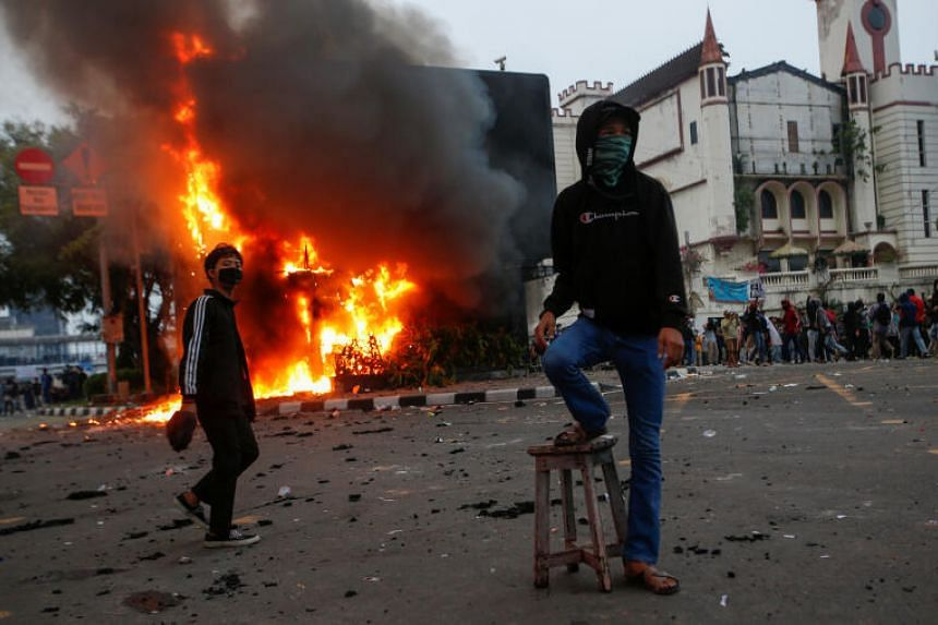 Demonstrators standing next to a burning police station in Jakarta, on Oct 8, 2020.