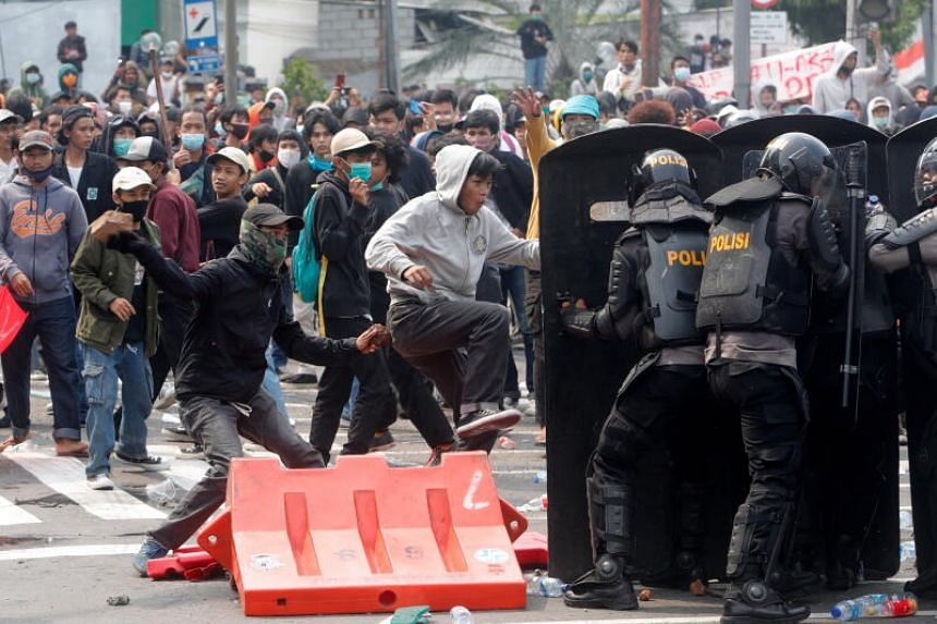 Protesters throwing stones at anti-riot police officers during a demonstration against the Omnibus law in Jakarta on Oct 8, 2020.