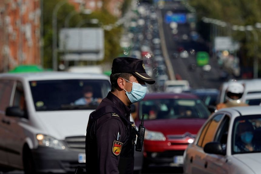 A police officer wearing a protective mask stands at a traffic checkpoint during a partial lockdown in Madrid, Spain.