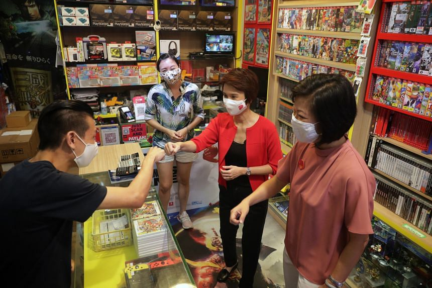 Senior Minister of State Sim Ann (right) and Minister of State Low Yen Ling visiting Gamewerks Singapore yesterday, where they met shop staff Stanley Yao and Jane Tang (background). The games store in Clementi Avenue 3 is among the heartland business