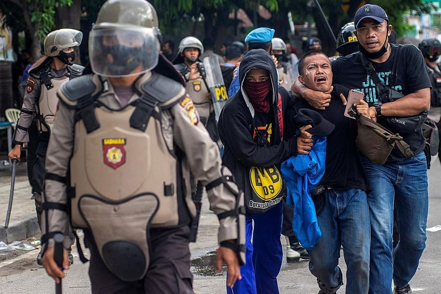 Plain-clothes policemen detaining a student protester at a rally against Indonesia's controversial job creation law in Palu, Central Sulawesi province, on Thursday. Over 3,800 people have been held nationwide during rallies this week that at times tu