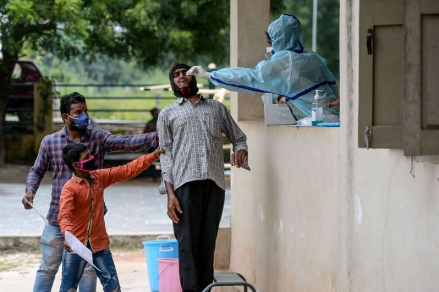 Residents hold a man as a health worker collects a swab sample from him to test for Covid-19 on the outskirts of Hyderabad, on Oct 8, 2020.