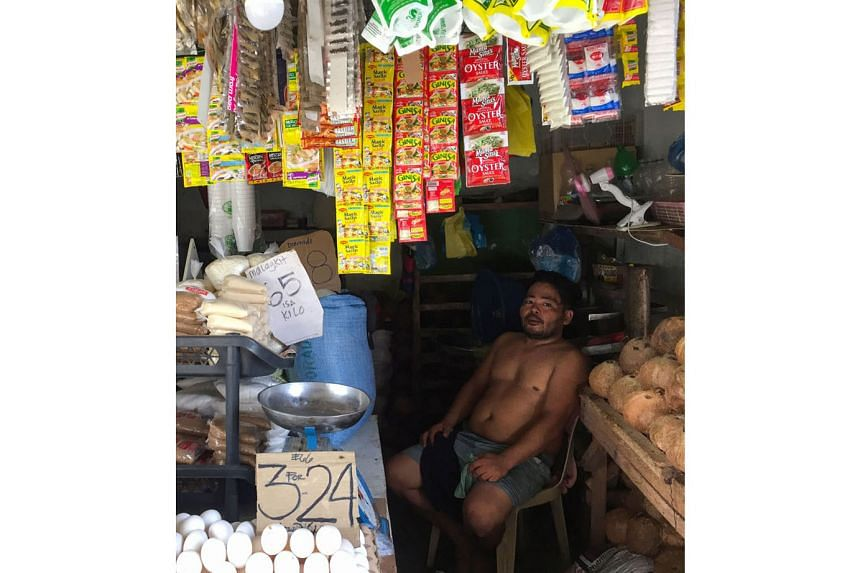 "Mr Richard Pontillas resting in his family-owned ""sari-sari"" or provision shop in Quezon City, the Philippines, in August. The liquid goods he sells used to be packaged in glass, but now he stocks them in plastic sachets. Employees sorting plastic bo"
