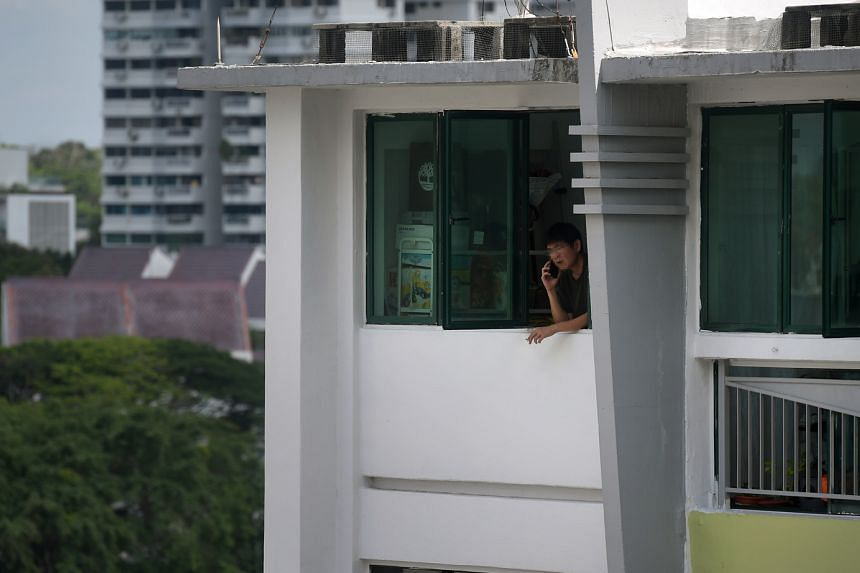 A man smoking at the window of a Housing Board flat in Toa Payoh in April. Complaints about second-hand smoke in residential areas have recently risen, according to the Municipal Services Office.