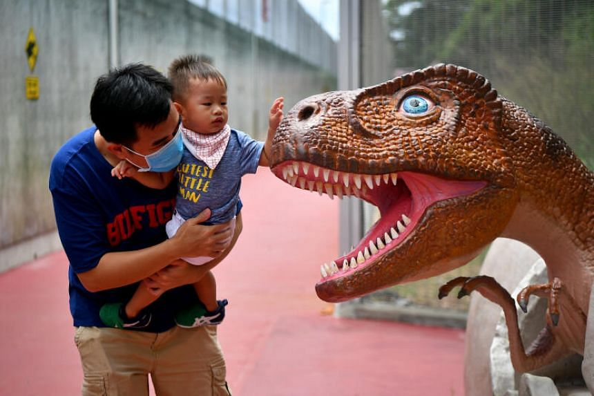 A father letting his child play with a dinosaur at the Changi Jurassic Mile, on Oct 11, 2020.