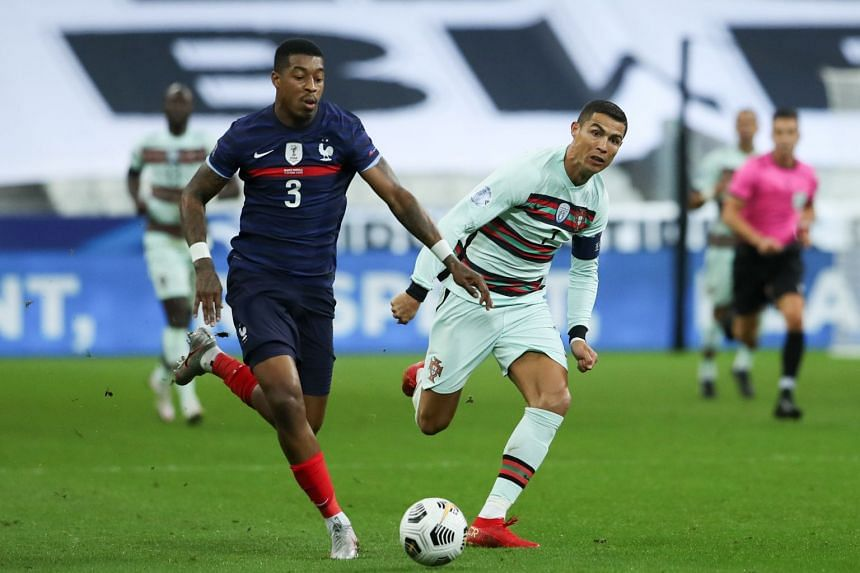 (From left) France's Presnel Kimpembe fights for the ball with Portugal's Cristiano Ronaldo.