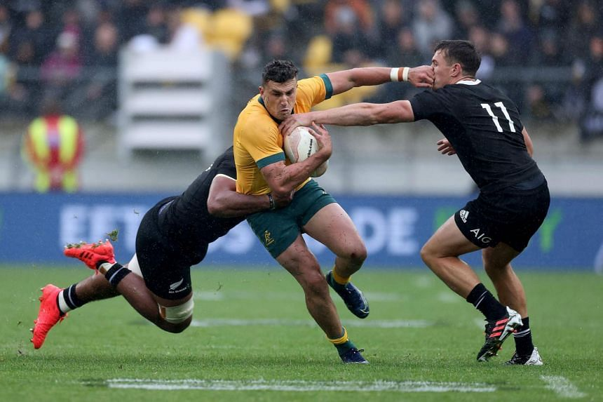 Australia's Tomas Banks (centre) is tackled by New Zealand's Hoskins Sotutu (left) and George Bridge during their rugby match in Wellington on Oct 11, 2020.