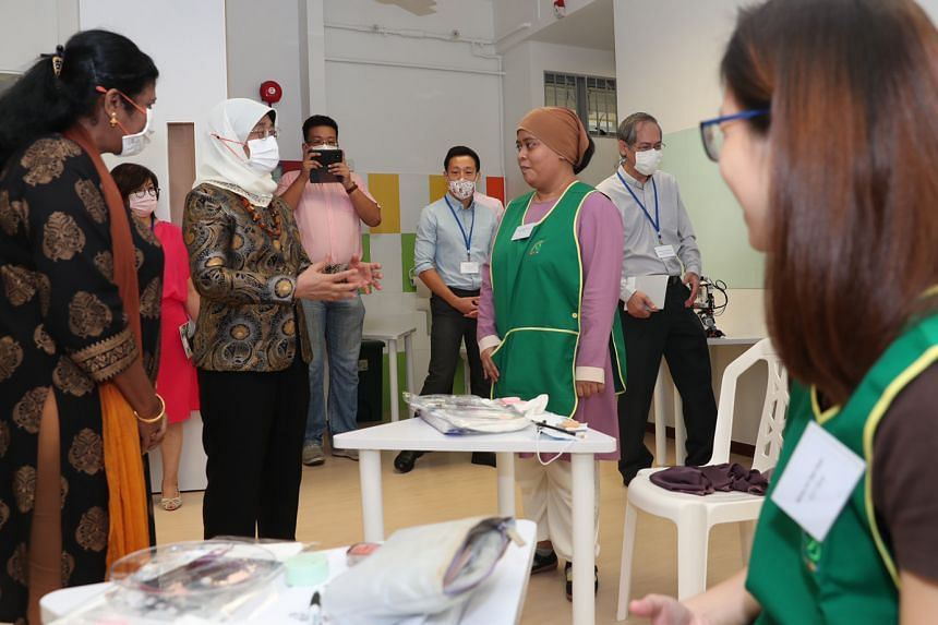 President Halimah Yacob speaking to a trainee from the Presbyterian Community Services' EduCarer Aide Training programme during a visit to the Providence Care Centre in Jurong East last Friday.