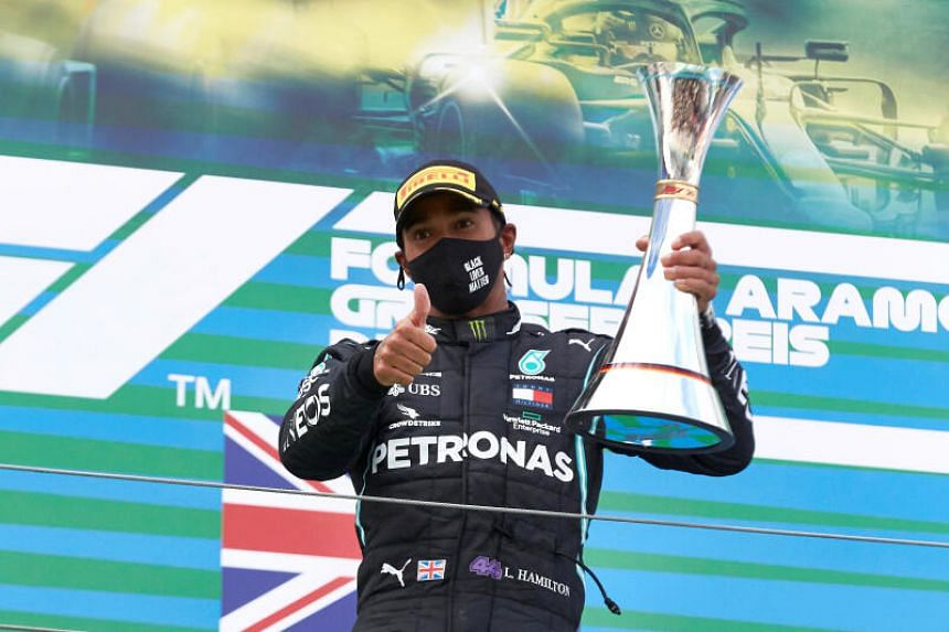 Mercedes' Lewis Hamilton celebrates with a trophy on the podium after winning the Eifel Grand Prix on Oct 11, 2020.