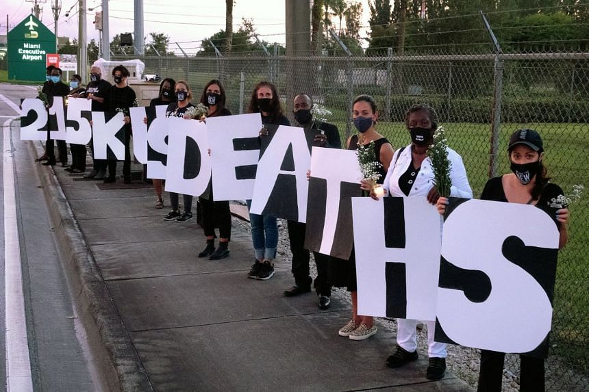 Activists at a candlelight vigil on Sunday to remember those who have lost their lives as a result of the Covid-19 disease and to protest against US President Donald Trump's campaign, in front of the Miami airport in Florida.