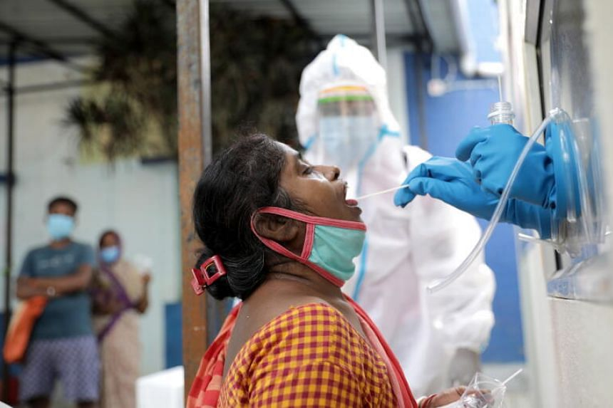Health officials taking a swab sample from a woman in Kolkata on Oct 13, 2020.