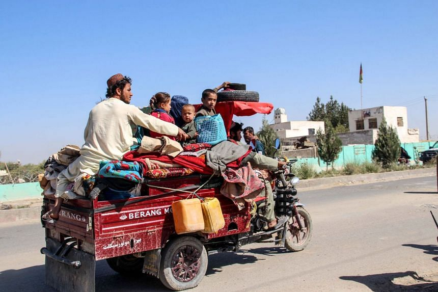 People flee with their belongings during ongoing clashes between Taleban fighters and Afghan security forces, in Helmand, Afghanistan, on Oct 14, 2020.