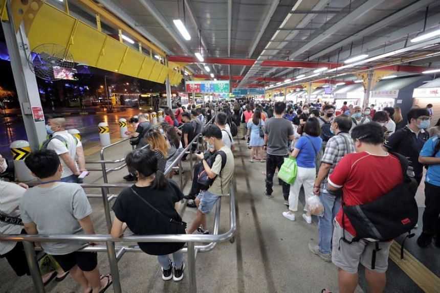 Commuters at Jurong East interchange waiting to take the bus after a power fault disrupted train services on Oct 14, 2020.