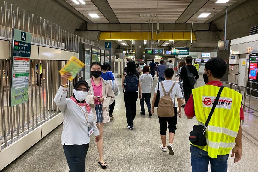 Staff guiding commuters through Jurong East station after train services were restored, at about 10.35pm, on Oct 14, 2020.